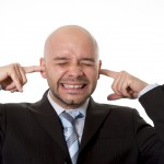 Brazilian businessman wearing suit and tie in stress covering his ears with fingers hoping for noise to stop