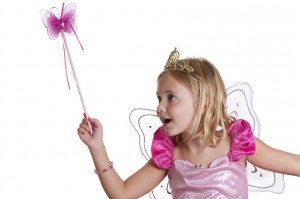 A young girl dressed up as a pink fairy with crown, wand, and wings casts a spell.