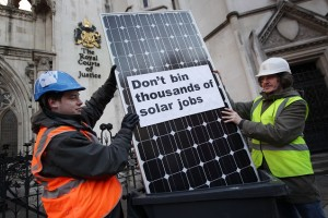 LONDON, ENGLAND - DECEMBER 15:  Campaigners Eliot Davies (L) and Jason Arnold pose with a solar panel in a wheelie bin outside The High Court on December 15, 2011 in London, England. Friends of the Earth are applying to challenge government plans to cut financial incentives for solar electricity.  (Photo by Peter Macdiarmid/Getty Images)