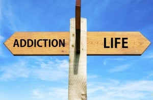 Wooden signpost with two opposite arrows over clear blue sky, Addiction and Life signs, Choice conceptual image