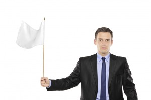 Young businessman waving a white flag isolated on white background