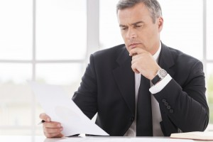 Businessman examining contract. Thoughtful mature man in formalwear holding hand on chin while examining document and sitting at working place