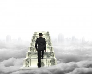 Businessman climbing the money stairs with gray cityscape cloudscape