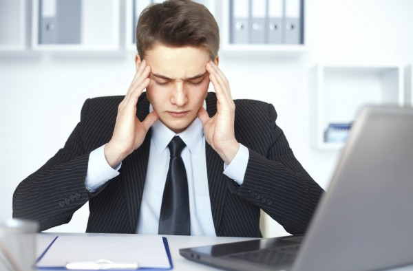 Tired young businessman in office